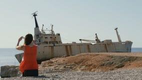Piękni kobiet spojrzenia przy shipwreck w Cypr zbiory wideo
