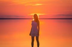 Piękni kobieta modela stojaki przed słońcem iść za horyzontem przy nadmorski Słonego jeziora Elton spokoju woda podczas zmierzchu Zdjęcia Stock