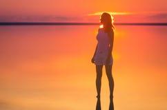 Piękni kobieta modela stojaki przed słońcem iść za horyzontem przy nadmorski Słonego jeziora Elton spokoju woda podczas zmierzchu Obraz Royalty Free