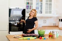 Piękni kobieta w ciąży narządzania muffins Obraz Stock