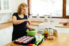 Piękni kobieta w ciąży narządzania muffins Obrazy Stock