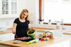 Piękni kobieta w ciąży narządzania muffins Zdjęcie Royalty Free