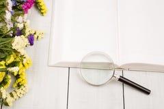 Piękni kolorowi kwiaty, otwarta puste miejsce książka i powiększać, - szkło obrazy stock