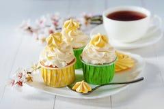 Piękni kwiaty na drewnianym stole z białym waniliowym capcake z bezami i filiżanką kawy, Obrazy Stock
