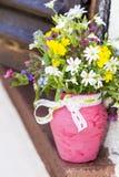 Piękni lasowi kwiaty w różowej wazie z faborkiem na drewnianej nadokiennej żaluzi Obrazy Royalty Free