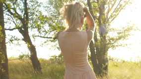 Piękni młoda kobieta spacery w zaświecają suknię w drewnach przy zmierzchem zbiory