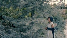 Piękni młoda kobieta stojaki w iglastym lesie i śpiewają piosenkę zbiory