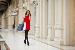 Piękni młodej kobiety mienia torba na zakupy chodzi w sklepie zdjęcia royalty free