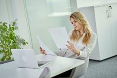 Piękni młodzi bizneswomanów spojrzenia przy dokumentami przy biurkiem Obraz Stock