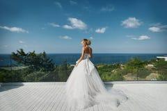 Piękni młodzi blondyny modelują dziewczyny w biel sukni pozyci z z powrotem kamera i patrzeć morze obrazy stock