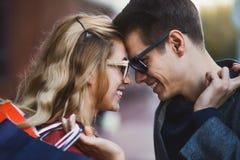 Piękni młodzi kochający pary przewożenia torba na zakupy i cieszyć się wpólnie zdjęcia stock
