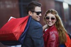 Piękni młodzi kochający pary przewożenia torba na zakupy i cieszyć się wpólnie zdjęcia royalty free