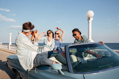 Piękni młodzi ludzie jedzie kabriolet i opowiada fotografie w lecie Fotografia Stock