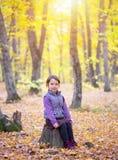 Piękni mała dziewczynka stojaki na bagażniku drzewny ono uśmiecha się obraz stock