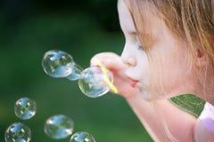 Piękni małej dziewczynki dmuchania bąble Fotografia Royalty Free
