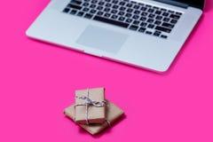 Piękni mali prezenty i chłodno laptop na cudownych menchiach z powrotem Obrazy Stock