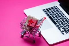 Piękni mali prezenty w wózek na zakupy i chłodno laptopie na wo Zdjęcie Stock