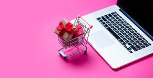 Piękni mali prezenty w wózek na zakupy i chłodno laptopie na wo Zdjęcie Royalty Free
