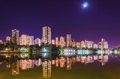 Piękni miast światła odbijali na wodzie jezioro przy nig Zdjęcia Stock