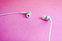 Piękni nowożytni cyfrowi plastikowi próżniowi biali hełmofony z drutami dla słuchać muzyka na purpurze różowią tło kosmos kopii obraz stock
