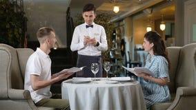 Piękni par spojrzenia Przez menu i kelnera Biorą rozkaz zbiory wideo