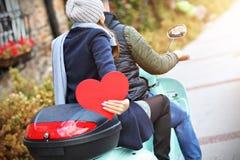 Piękni potomstwa dobierają się mień serca podczas gdy jadący hulajnogę w mieście w jesieni obraz stock
