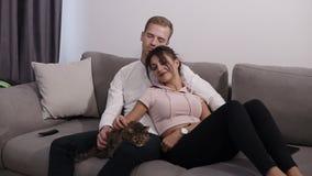 Piękni potomstwa dobierają się z ich kotem na ich żywej izbowej leżance Młody człowiek i kobieta pieścimy ich zwierzęcia domowego zbiory wideo