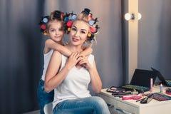 Piękni potomstwa macierzyści i jej córka z włosianymi curlers Obraz Stock