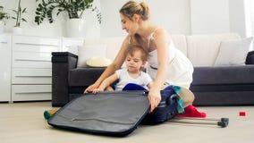 Piękni potomstwa matki i berbeć chłopiec kocowania walizka dla wakacji Obrazy Stock