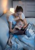 Piękni potomstwa matkują czytelniczą książkę jej dziecko w łóżku przy nocą obrazy royalty free