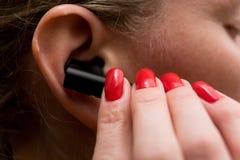 Piękni przygotowywający żeńscy palce wkładają słuchawki w twój ucho obrazy royalty free