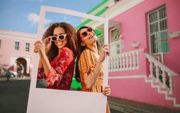 Piękni przyjaciele cieszy się outdoors z obrazek ramą fotografia stock