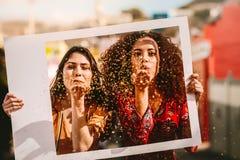 Piękni przyjaciele dmucha błyskotliwość przez pustej fotografii ramy zdjęcia stock