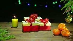 Piękni pudełka z prezentami obok choinki i płonącej świeczki na czarnym tle z światłami zbiory wideo