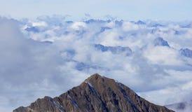 Piękni szczyty w Alps otaczających lekkimi białymi chmurami zdjęcia stock