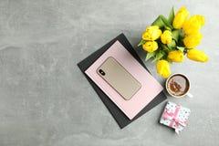 Piękni tulipany w wazie i smartphone z akcesoriami na szarym tle obrazy stock