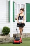 Piękni uśmiechnięci housemaid stojaki z gazonu kosiarzem zdjęcie royalty free