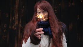 Piękni uśmiechnięci imbirowi młoda kobieta stojaki na brown tle z sparkler przy zmierzchem zdjęcie wideo