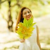 Piękni uśmiechnięci kobiety mienia jesieni liście w parku (pierwszy plany Fotografia Royalty Free
