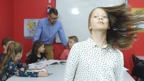Piękni uczennica zwroty w ramę, ucznie z nauczycielem na tle zdjęcie wideo