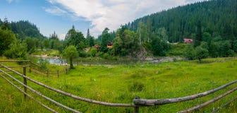 Piękni widoki teren górzysty z aktualną rzeką między niskimi bankami z zieloną trawą na jeden stronie i obrazy stock