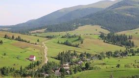 Piękni zieleni wzgórza i chałupa z czerwień dachem w wiosce zbiory wideo