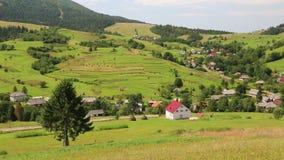 Piękni zieleni wzgórza i chałupa z czerwień dachem w wiosce zdjęcie wideo