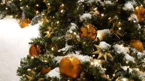 Pięknie dekorująca choinka z wielkimi piłkami, gwiazdami, girlandami i sztucznym śniegiem złocistymi i srebnymi, stoi zdjęcie wideo