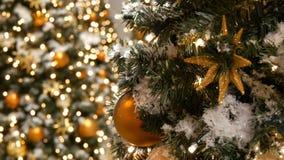 Pięknie dekorująca choinka z wielkimi piłkami, gwiazdami, girlandami i sztucznym śniegiem złocistymi i srebnymi, stoi zbiory