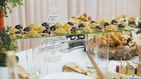 Pięknie dekorujący cateringu bankieta stół z różnymi jedzenie przekąskami, zakąskami na korporacyjnych bożych narodzeniach urodzi zbiory wideo