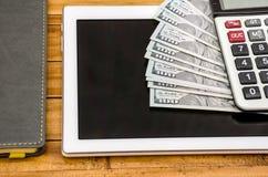 Pięknie fałdowi dolary na pastylce, kalkulatorze i notatniku, obraz royalty free