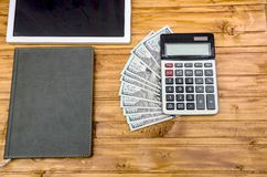 Pięknie fałdowi dolary na pastylce, kalkulatorze i notatniku, zdjęcia stock