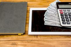 Pięknie fałdowi dolary na pastylce, kalkulatorze i notatniku, fotografia stock