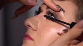 Piękno bar Młody piękny dziewczyna model siedzi w krześle Makeup artysta robi dziewczyny makeup Blondynka w pięknie zbiory